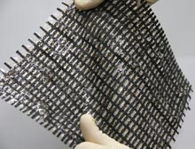 A researcher stretches a mesh of transistors connected by elastic conductors that were made at the University of Tokyo.